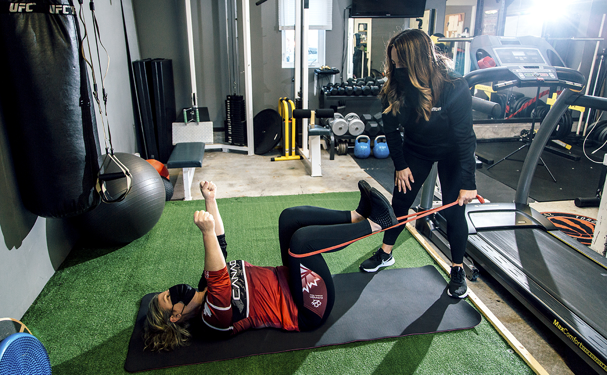 April Newman working with a client in her home gym