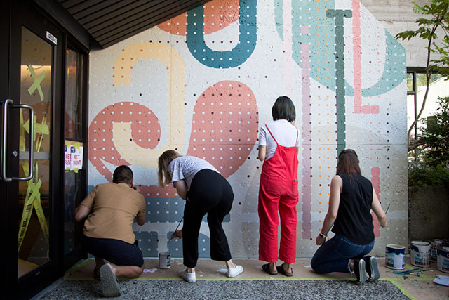 (From left) Ata Ojani, Brynn Staples, Emily Hyunh and Courtney Lamb paint their mural on Sept. 6, 2018. The IDEA School of Design students were commissioned to create one of ten murals to celebrate Capilano University's 50th anniversary. Check out our project (add link here to mural story) on the mural artists.