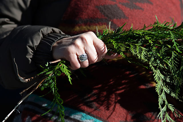 Noelle Natraoro holds a cedar brush during the canoe legacy project log blessing ceremony on Feb. 25.