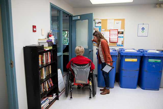 Jo Anthony, left, enters a room with the help of CapU student Alecia Ferreira at the North Shore Neighbourhood House in North Vancouver on Nov. 20, 2019. As part of the Unified Grant research funding program, CapU students are providing augmentative communication support to North Shore stroke survivors. (Photo by Taehoon Kim)