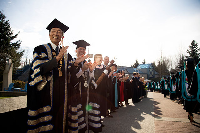 Chancellor David T. Fung, left, welcomes students during Convocation ceremonies on Feb. 21, 2020. The February ceremonies marked Fung's last Convocation as Chancellor. (Photo by Tae Hoon Kim)